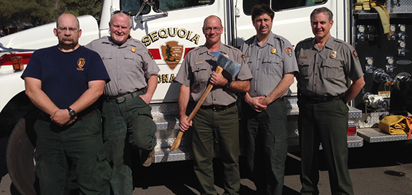 Sequoia and Kings Canyon fire staff pose for a photo with fire fighting tools.