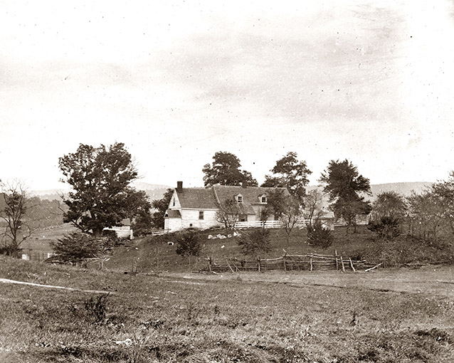Historic images of a farmhouse and landscape, with several trees and a marshy area to the left.