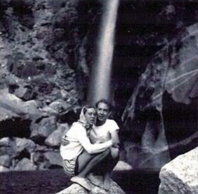 Couple stands in front of Yosemite falls in the 1950s.
