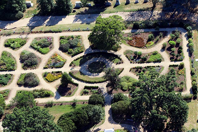 Aerial view of a formal garden, with symmetrical paths dividing garden beds.