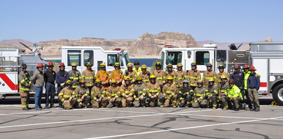 Large group of firefighters in uniform in front of fire engines and a mountain vista