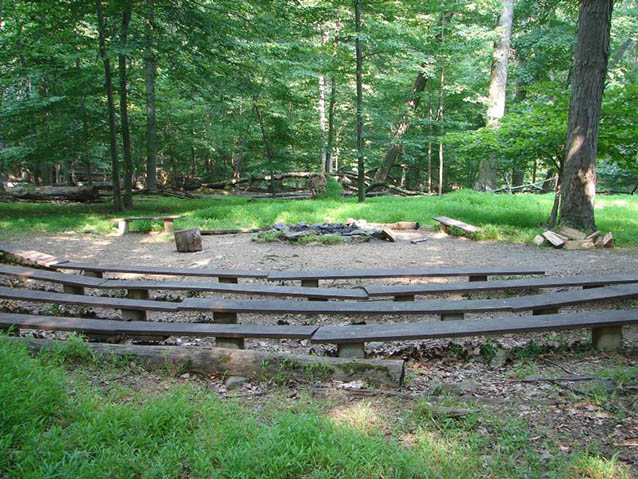 Wooden benches form a semi-circle around a campfire area, surrounded by forest