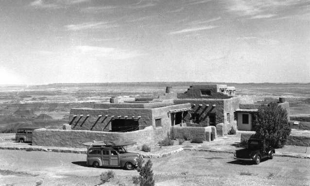 Several 1940s vehicles in the parking area in front of a low adobe structure