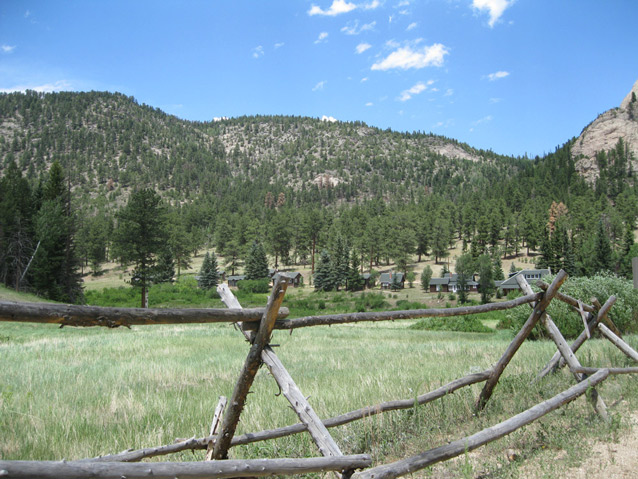 A wooden fence frames the landscape, including grassy area, ranch buildings, and pine-covered hills.