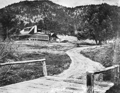 Historic photo of a narrow wooden bridge and dirt road leading to a large ranch house.