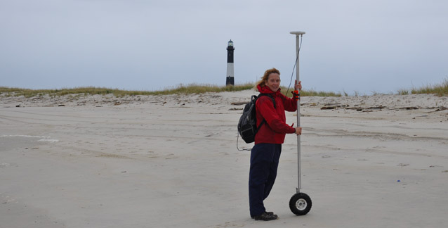 A scientist holds a GPS unit on a pole with a wheel on the beach.