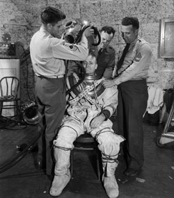 Ray H. Wright putting on a diving suit to protect him from high pressure, temperature and noise