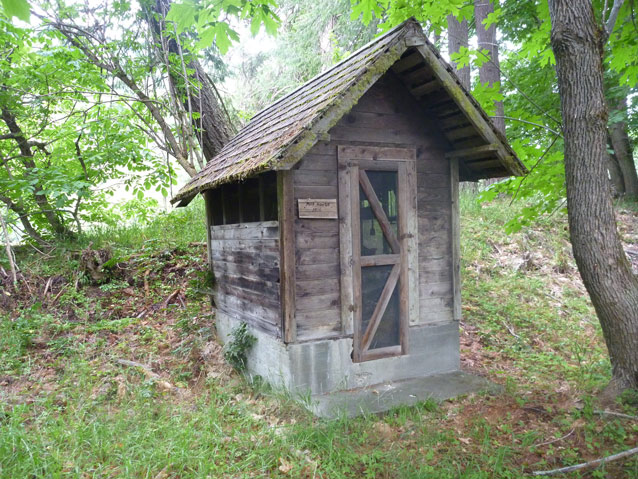 A small, square wooden building with a peaked roof and one door in a wooded area