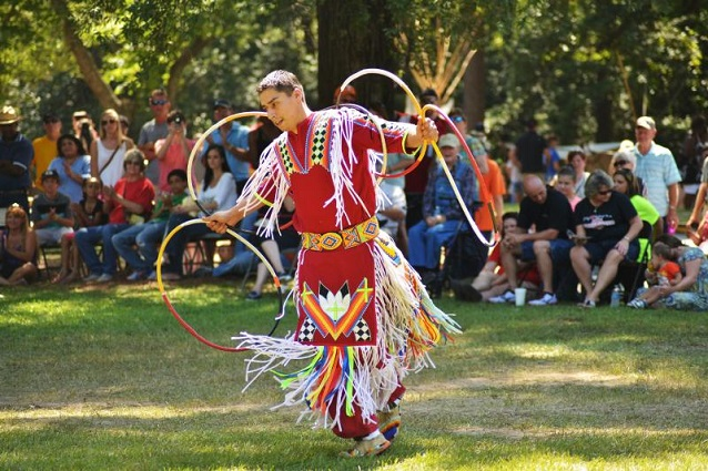 Native American hoop dancer performing for a crowd