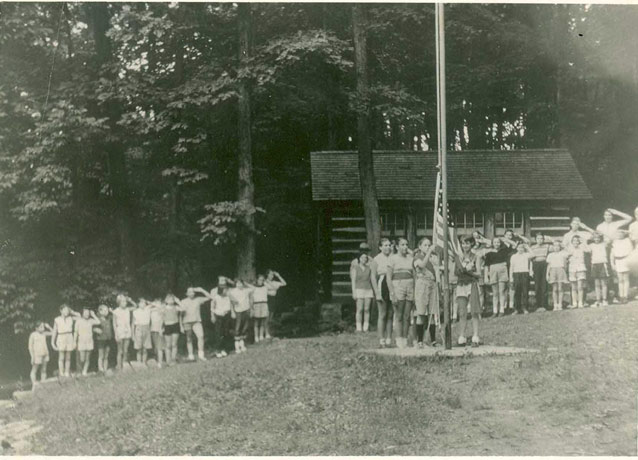 A crowd of young people, near a cabin, salutes as several girls attach the flag to a pole.
