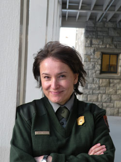 A smiling woman in NPS uniform with crossed arms