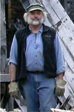 A man with a grey beard, work gloves, cap, blue jeans, and unzipped fleece vest.