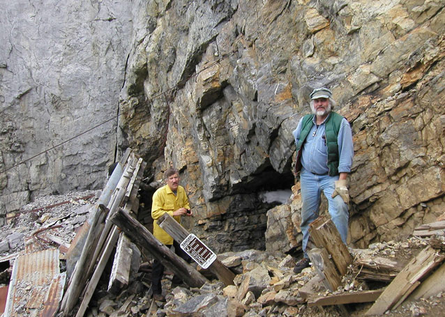 Two men stand beside a rough rock face, with wood and metal debris scattered around.