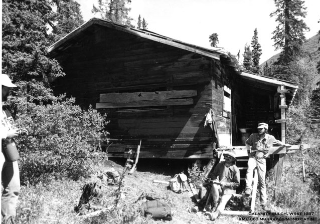 Three men with hats on the front steps of a wood cabin, surrounded by trees and hills