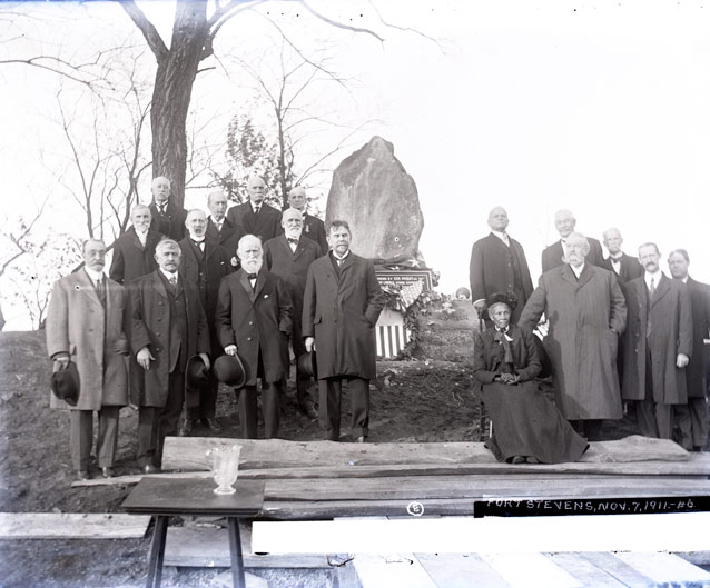 A group of men in overcoats and a seated woman in a long, dark dress pose beside a monument.