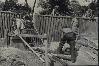 A crew of young men in work attire with scattered logs and a partially-built log fortification
