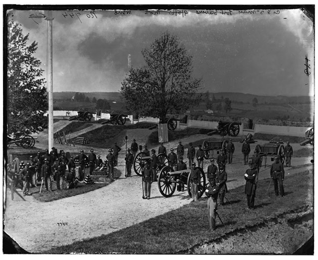 Historic image showing uniformed soldiers gathered around cannons and fortifications