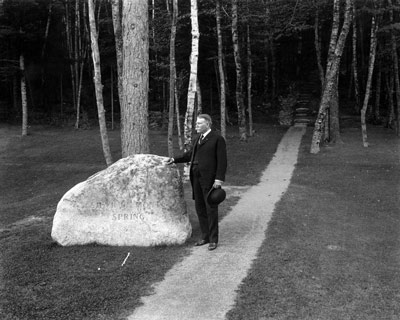 A man in a dark suit, holding a bowler hat, stands with one hand on a large boulder.
