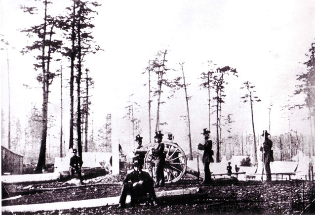 Grainy image of soldiers, a canon, and a scattering of tents in an open forest
