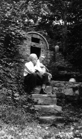 A man sits on a set of stone stairs, hand on his chin and facing away from the camera into trees