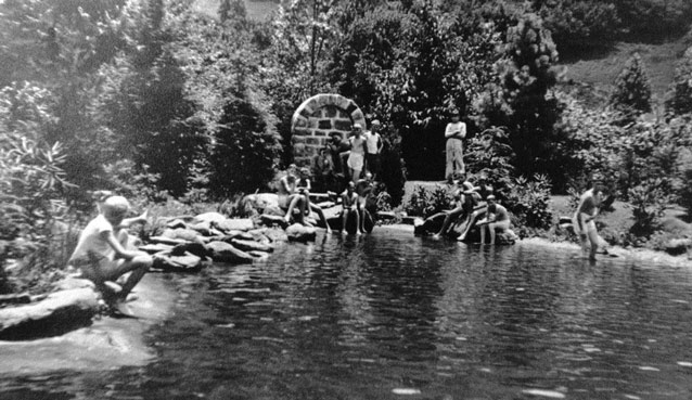 Bathers gather at the edge of a pool of water, near a brick structure marking a spring