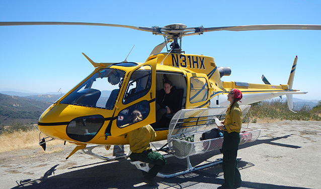 Helitack crewmembers standing by a yellow helicopter.