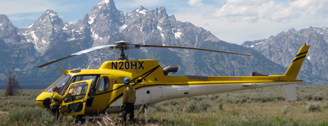 Two pilots and a park service helicopter in a field with mountains in the background.