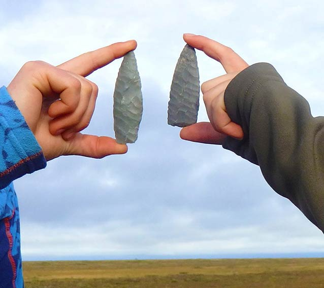 two stone arrow heads, roughly 5 inches long, being held up by two people