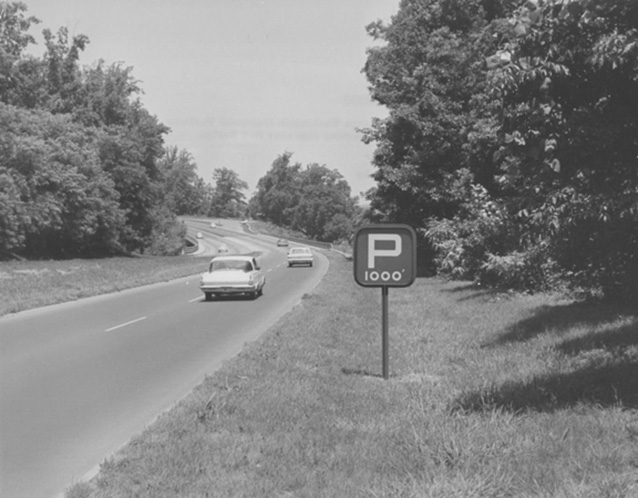 Historic image of a car driving on a parkway, bordered by a grassy shoulder and trees