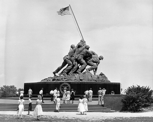 Women and men stand at the base of a monument, depicting U.S. armed forces raising a flag.