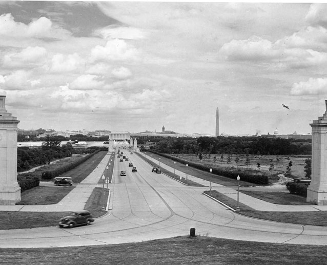 Cars cross a bridge toward Lincoln Memorial on a wide road, bordered by landscaping and lampposts