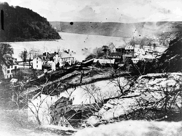 Civil War-era photograph of Virginius Island shows buildings beside the river and hills.
