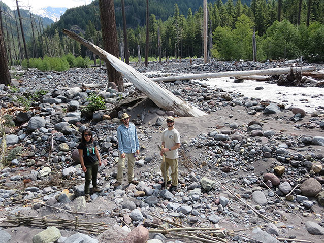 Interns standing in rocky river bed