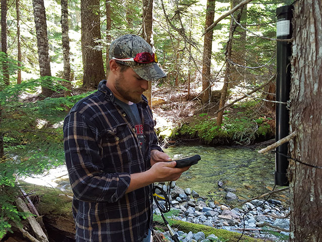 Intern with hand held gps standing near stream