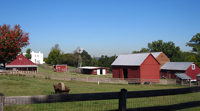 Farm structures of various sizes are scattered on the landscape under a clear sky.