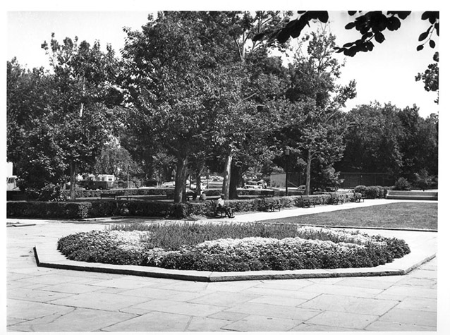 A low-growing flower bed in a central stone plaza with trees, hedges, and lawn beyond.