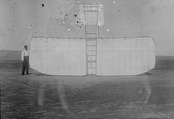 Orville Wright at left wing end of upended glider, bottom view; Kitty Hawk, North Carolina