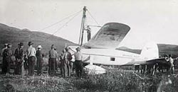 Wiley Post standing on his airplane the Winnie Mae,