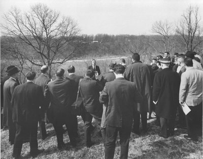 A man speaks to a crowd of men in suits and overcoats, all standing in front of a wide view.