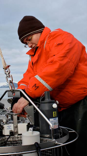 A woman in a bright orange jacket adjusting some kind of scientific equipment