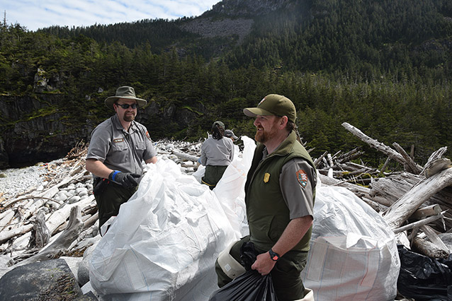 park rangers putting trash into plastic bags