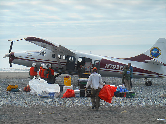 people loading plastic bags into a small plane on a rocky beach