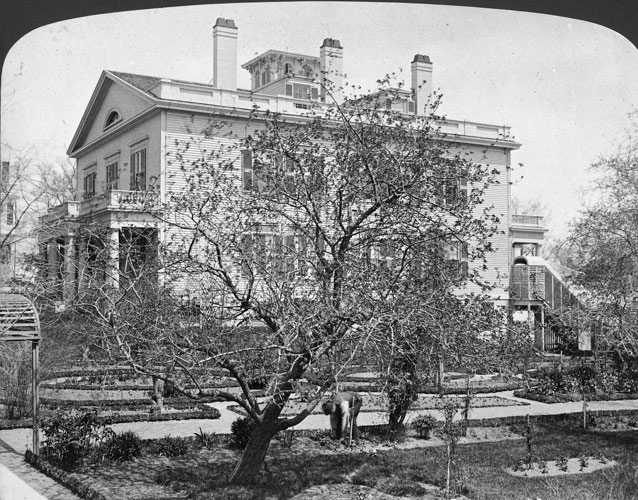 1870s photo of a branching apple tree and garden plots beside large, two story rectangular house