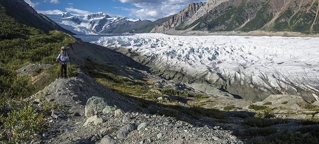 A hiker walks on an old lateral moraine of the Root Glacier (Wrangell-St. Elias National Park, AK)