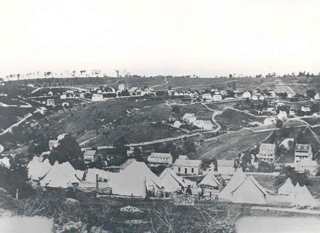 Historic photo of tent camp, with rolling rural landscape dotted with houses beyond.