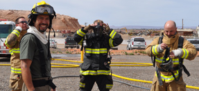 A firefighter looks at the camera while other firefighters put on full protective gear
