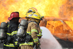 Fire crew aggressively controls a vehicle fire for a simulated rescue exercise.