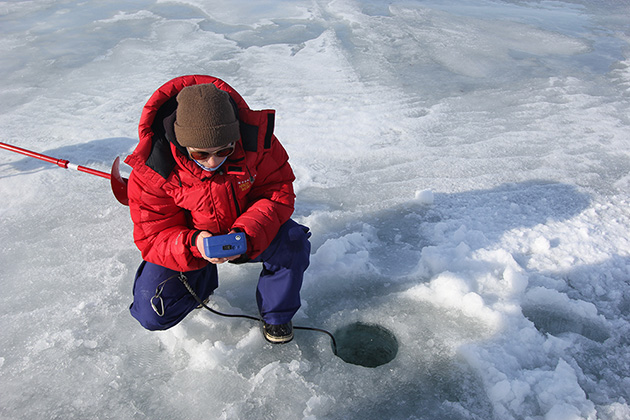 woman in red parka kneeling by a hole in ice