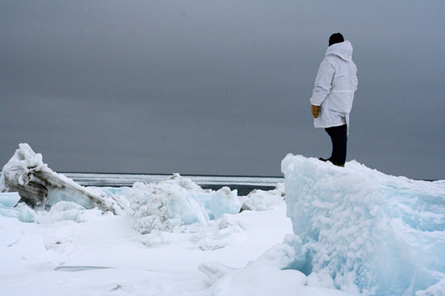 man in a white parka standing on large block of ice looking toward the ocean