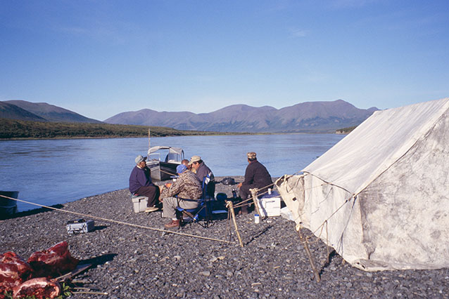 people sitting near a canvas tent near a large river